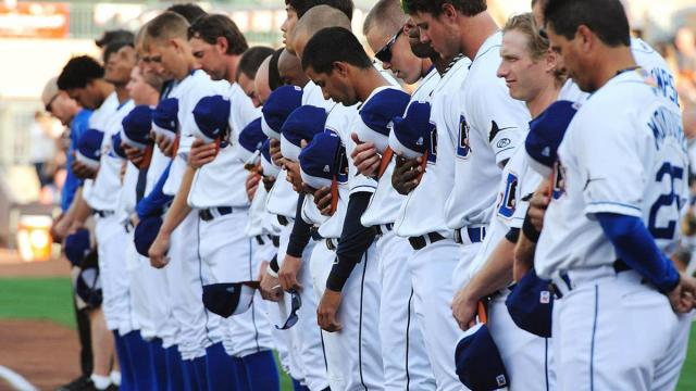 The Durham Bulls line up during the singing of the National Anthem prior to the team's home opener Monday, April 8, 2013 at the Durham Bulls Athletic Park.  This year marks the 18th season for the ball club to play in their current home. (Photo by Jeffrey A. Camarati)