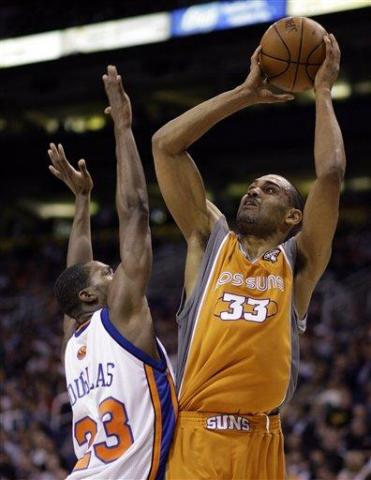 Phoenix Suns forward Grant Hill, right, attempts a field goal over New York Knicks guard Toney Douglas, left, in the third quarter of an NBA basketball game Friday, March 26, 2010, in Phoenix. The Suns won 132-96. (AP Photo/Paul Connors)