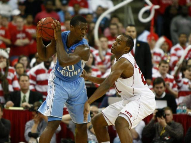 C.J. Williams (21) plays defense against Harrison Barnes (40) during the UNC vs. NC State game on February 21, 2012 in Raleigh, North Carolina.<br/>Photographer: Jerome Carpenter