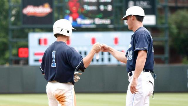 Robert Woodard gives Tommy Coyle a first bump at first during the UNC vs. ECU regional game on June 3, 2012 in Chapel Hill, NC.