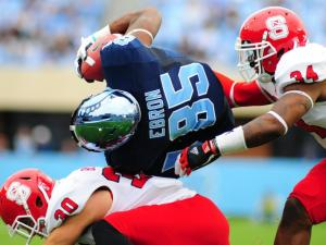 Eric Ebron (85) is tackled by Brandan Bishop (30) and Rickey Dowdy (34) during the North Carolina Tar Heels vs. N.C. State Wolfpack NCAA football game, Saturday, October 27, 2012 in Chapel Hill, N.C.