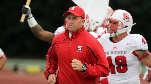 N.C. State coach Dave Doeren leads his team onto the field for the Wolfpack's visit to Duke on November 9, 2013 in Durham, NC.  Duke defeated N.C. State 38-20 (Photo by Jack Morton).