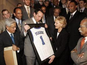 Duke men's basketball coach Mike Krzyzewski, center left, gives North Carolina Gov. Bev Perdue a Duke jersey during a ceremony honoring at Duke in Raleigh, N.C., Wednesday, April 21, 2010, for winning this year's NCAA title. (AP Photo/Jim R. Bounds)