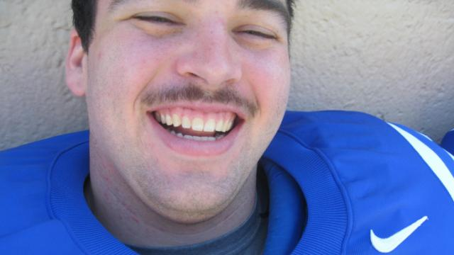 Duke offensive lineman Perry Simmons smiles wide for the camera at Photo Day.