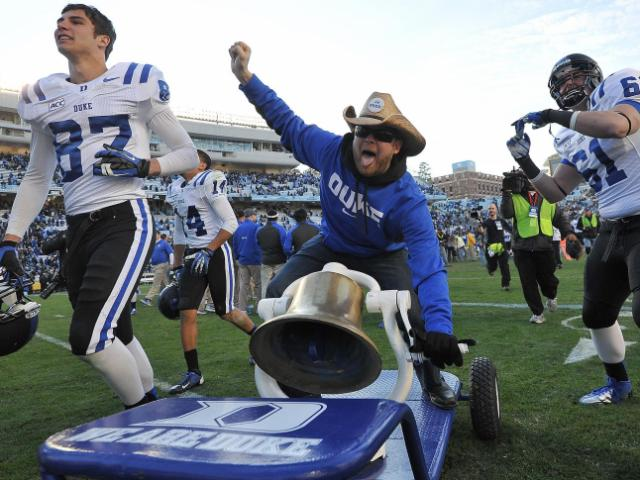 "A Duke fan rides the ""Victory Bell"" following action at Kenan Stadium between the University of North Carolina Tar Heels and the Duke University Blue Devils on November 30, 2013 in Chapel Hill, NC."