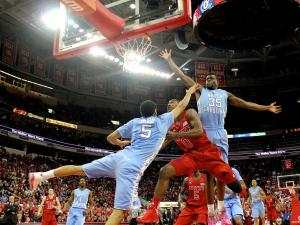 Rodney Purvis (0) hangs in the air to get by Marcus Paige (5) and Reggie Bullock (35) during the UNC vs. NC State game on January 26, 2013 in Raleigh, North Carolina.