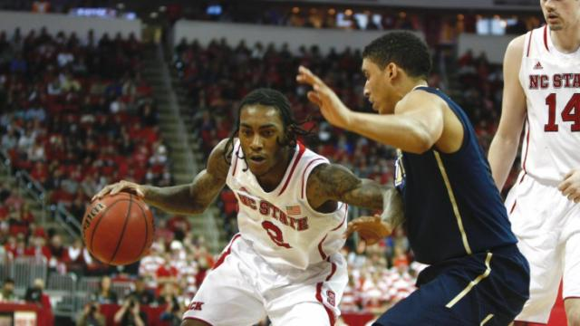 "Anthony ""Cat"" Barber (2) drives against a Pitt defender. Pitt defeated NC State 74-62 on January 4, 2014 at the PNC Arena in Raleigh, North Carolina.  Photo by: Jerome Carpenter."