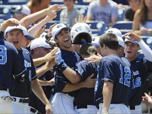 North Carolina players embrace Brian Holberton, center right with back to camera, after he hit a two-run home run against LSU in the first inning of an NCAA College World Series elimination baseball game in Omaha, Neb., Tuesday, June 18, 2013. (AP Photo/Eric Francis)