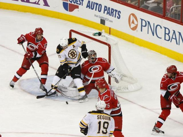 Patrice Bergeron (37) tries to hammer the puck by Cam Ward (30) during the Bruins vs. Hurricanes game on January 28, 2013 in Raleigh, NC.
