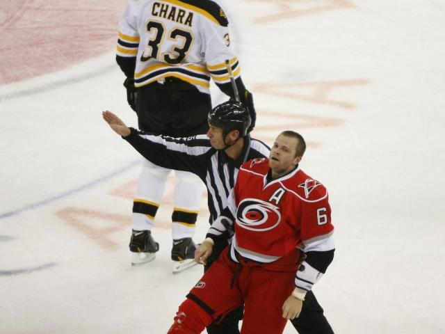 Tim Gleason (6) is escorted to the box for fighting during the Bruins vs. Hurricanes game on January 28, 2013 in Raleigh, NC. <br/>Photographer: Jerome Carpenter