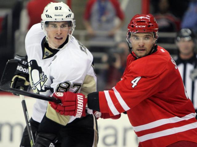Pittsburgh's Sidney Crosby (left) and Carolina's Andrej Sekera during the Penguins' 3-1 road victory over the Carolina Hurricanes at PNC Arena on Monday, October 28, 2013 in Raleigh, NC (Photo by Jack Morton).