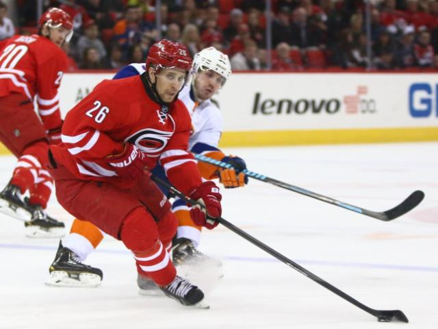 John-Michael Liles (26) slows down to control the puck. The Islanders defeated the Hurricanes 5-4 on March 25, 2014 at the PNC Arena in Raleigh, North Carolina. Photo by: Jerome Carpenter<br/>Photographer: Jerome  Carpenter