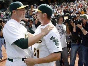 Oakland Athletics pitcher Dallas Braden, right, is congratulated by teammate Landon Powel after throwing a perfect game against the Tampa Bay Rays during a baseball game in Oakland, Calif., Sunday, May 9, 2010. Oakland won 4-0. (AP Photo/Dino Vournas)