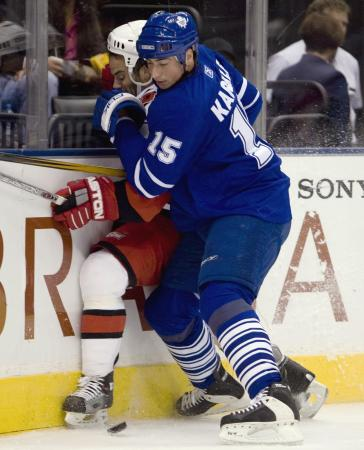 Toronto Maple Leafs defenseman Tomas Kaberle (15), of the Czech Republic, ties up Carolina Hurricanes' Chad LaRose along the board during the first period of their NHL hockey game in Toronto, Tuesday Oct. 9, 2007. (AP Photo/Adrian Wyld, The Canadian Press)