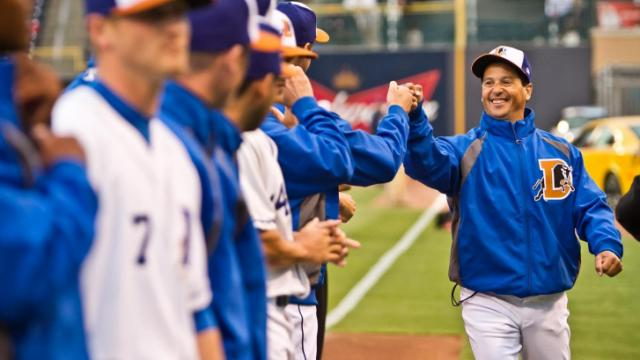 MFILE: anager Charlie Montoyo fist bumps players on his 2012 Durham Bulls team.