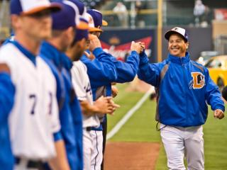 Manager Charlie Montoyo fist bumps players on his 2012 Durham Bulls team.
