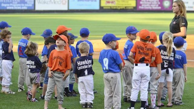Nash County youth baseball players get ready to accompany the Carolina Mudcats onto the field for the starting lineups of the second game of Tuesday's doubleheader at Five County Stadium. The Mudcats split with the Potomac Nationals.