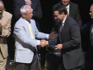 UNC men's head basketball coach Roy Williams congratulates Duke men's basketball coach Mike Krzyzewski after he receives the Naismith Good Sportsmanship Award.