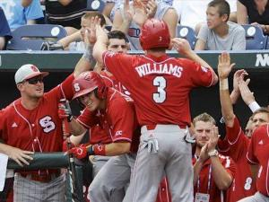 North Carolina State's Brett Williams (3) is congratulated at the dugout after scoring a run against North Carolina on a single by Bryan Adametz in the third inning of an NCAA College World Series baseball game in Omaha, Neb., Sunday, June 16, 2013. (AP Photo/Eric Francis)