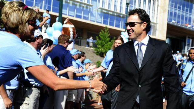 UNC head coach Larry Fedora greets fans during the Victory Walk before play between the University of North Carolina Tar Heels and the East Carolina Pirates on Septempber 28, 2013 in Chapel Hill, NC.