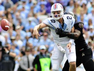 Bryn Renner (2) is hit by ECU linebacker Ty Holmes (49) during play at Kenan Stadium between the University of North Carolina Tar Heels and the East Carolina Pirates on Septempber 28, 2013 in Chapel Hill, NC.