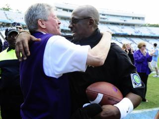 ECU chancellor Steve Ballard and head coach Ruffin McNeill embrace following play at Kenan Stadium between the University of North Carolina Tar Heels and the East Carolina Pirates on Septempber 28, 2013 in Chapel Hill, NC.