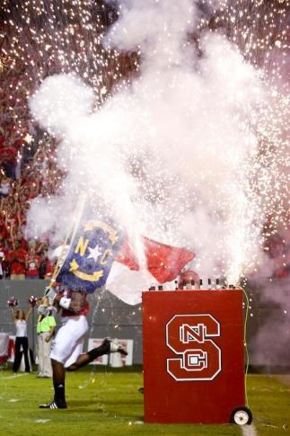 The NC State football team runs onto the field prior to their game against USF.