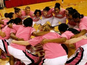 The N.C. State women's basketball team huddles up at midcourt before their first game since their head coach, Kay Yow, died from breast cancer.