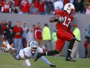 Owen Spencer of N.C. State hops over a tackle from Kendric Burney of North Carolina on November 28, 2009.