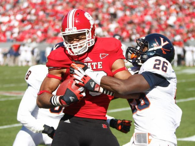Quintin Payton (88) is met by two defenders after securing a catch during the Virginia vs. NC State game on November 3, 2012 in Raleigh, North Carolina.<br/>Photographer: Jerome Carpenter