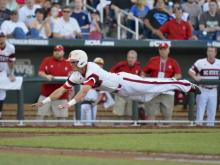 North Carolina State's Jake Armstrong leaps towards home plate before being tagged out by UCLA pitcher Nick Vander Tuig, following a single by Trea Turner in the third inning of an NCAA College World Series game in Omaha, Neb., Tuesday, June 18, 2013. (AP Photo/Ted Kirk)