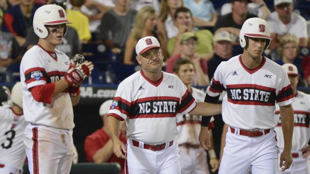North Carolina State coach Elliott Avent, center, follows his team against UCLA in the ninth inning of an NCAA College World Series baseball game in Omaha, Neb., Tuesday, June 18, 2013. UCLA won 2-1. (AP Photo/Ted Kirk)