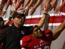 Coach Dave Doeren  high fives the fans after the Clemson vs. NC State game on September 19, 2013 in Raleigh, North Carolina.