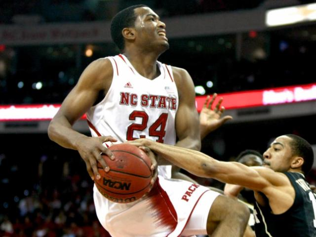 Coron Williams (13) commits a foul against T.J. Warren (24). NC State defeated Wake Forest 82-67 at the PNC Arena in Raleigh, North Carolina on February 11, 2014. Photo by: Jerome Carpenter. <br/>Photographer: Jerome  Carpenter