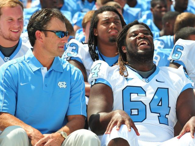 Head coach Larry Fedora and senior guard Jonathan Cooper (64) laugh before the group picture during the University of North Carolina Football media day, Saturday, August 4, 2012. <br/>Photographer: Will Bratton