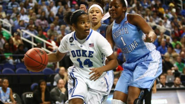 Ka'lia Johnson (14) dribbles away from a couple of Tar Heel defenders. Duke defeated North Carolina in the Semifinal round of the 2014 Women's ACC Basketball Tournament on March 8, 2014 in Greensboro, North Carolina. Photo by: Jerome Carpenter