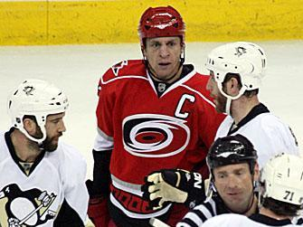 A linesman steps in to separate Hurricanes captain Rod Brind'Amour and Penguins superstar Evgeni Malkin.