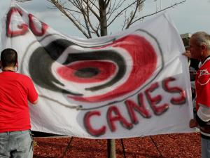 A guy signs a banner Saturday afternoon before the Carolina Hurricanes last Saturday home game. (photo by Wes Hight).