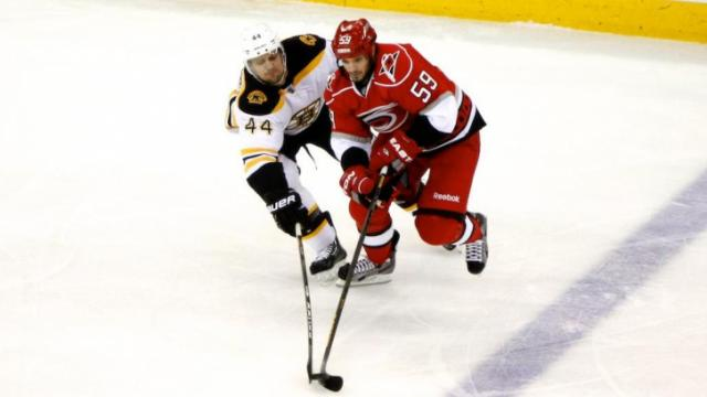 Chad LaRose (59) and Dennis Seidenberg (44) both reach for the puck during the Bruins vs. Hurricanes game on January 28, 2013 in Raleigh, NC.