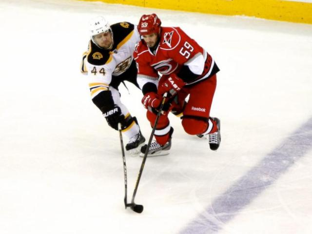 Chad LaRose (59) and Dennis Seidenberg (44) both reach for the puck during the Bruins vs. Hurricanes game on January 28, 2013 in Raleigh, NC. <br/>Photographer: Jerome Carpenter
