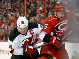 New Jersey Devils defenseman Bryce Salvador (24) and Carolina Hurricanes right wing Tuomo Ruutu (15) work the boards as the Devils defeated the Hurricanes 4 to 1 at PNC Arena in Raleigh, NC Thursday March 21, 2013 (Photo by Jack Tarr)