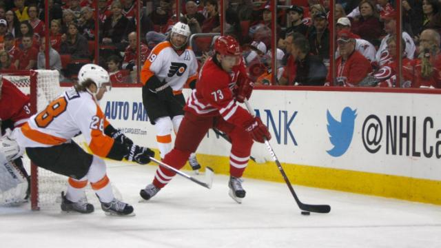 Brett Bellemore (73) skates away from a couple of Flyers wingers during the Flyers vs. Hurricanes game on October 6, 2013 in Raleigh, NC.