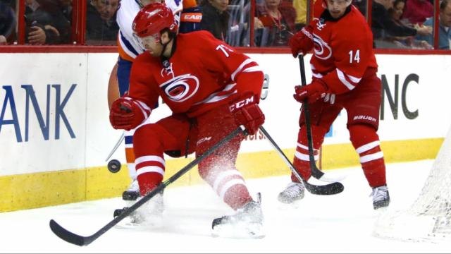 Brett Bellemore (73) and Kyle Okposo (21) battle on the boards. The Islanders defeated the Hurricanes 5-4 on March 25, 2014 at the PNC Arena in Raleigh, North Carolina. Photo by: Jerome Carpenter