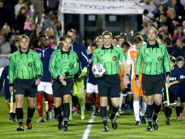 The officials lead the teams onto the field before the start of the game. The Carolina RailHawks defeated the Indy Eleven by a score of 3-1 at Wake Med Soccer Park in Cary, North Carolina on October 30, 2015. (Photo by: Jerome Carpenter/WRAL Contributor)
